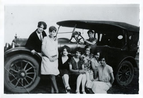 Several young people pose in a 1920s automobile